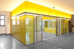 Edoors Produkte – Schiebetüranlagen, beschriftete Glas- Schiebetür vor gelber Wand